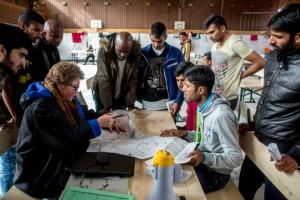 Une volontaire aide les réfugiés à se localiser sur la carte de la ville. En Allemagne.               Crédits : Michael Bunel / CIRIC