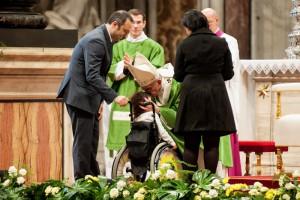 Le pape François embrassant un enfant malade, lors de la messe de clôture du synode sur la famille.  Copyright : M.MIGLIORATO/CPP/CIRIC